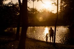 Father and son playing near the lake in the mountains of at the sunset time stock photos