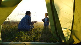 Father with son are playing near a tent on sunset stock footage