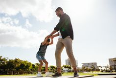 Father and son playing outdoors. Cheerful men playing with his son at a park. Father holding hands of his child in playful mood outdoors Royalty Free Stock Photo
