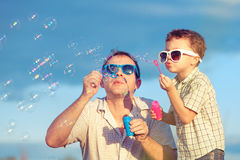 Father and son playing in the park at the day time. Concept of friendly family. Picture made on the background of blue sky stock photos