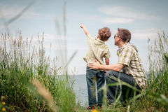 Father and son playing at the park near lake at the day time. Royalty Free Stock Photography
