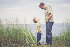 Father and son playing at the park near lake at the day time. Stock Photos