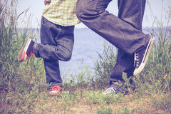 Father and son playing at the park near lake at the day time. Royalty Free Stock Image