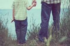 Father and son playing at the park near lake at the day time. Royalty Free Stock Images