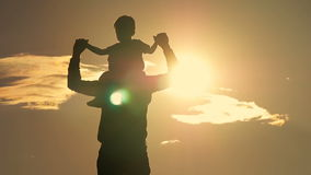 Father and son playing in the park at sunset silhouette of a happy family stock footage