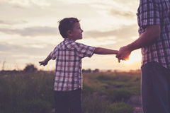 Father and son playing in the park at the sunset time. Royalty Free Stock Photography
