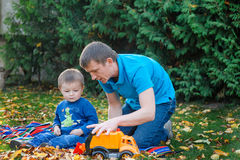 Father and son playing in the park toy car in a park on the gras Royalty Free Stock Image