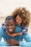Father and son playing piggyback on beach. Smiling at camera Stock Photography