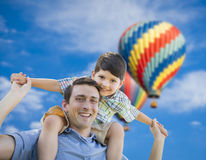 Father and Son Playing Piggyback with Hot Air Balloons Behind Stock Photography