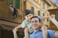 Father and Son Playing Piggyback on Streets of France Stock Image
