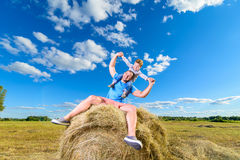 Father and son playing on a pile of hay Royalty Free Stock Photos