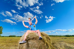 Father and son playing on a pile of hay Stock Images