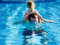 Father and son playing in the pool Royalty Free Stock Images