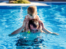 Father and son playing in the pool Stock Image