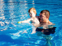Father and son playing in the pool Royalty Free Stock Photos