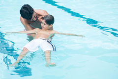 Father and son playing in pool Royalty Free Stock Image