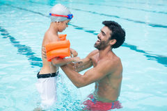 Father and son playing in pool Royalty Free Stock Images