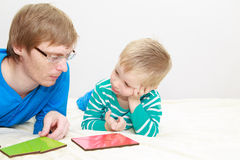 Father and son playing with puzzle Stock Images