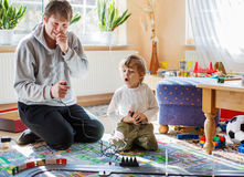 Father and son playing with racing cars on racetrack, indoors, t Stock Images