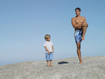Father and son (4-6) playing on rock near beach, smiling, man in swimming shorts standing on one leg Royalty Free Stock Photo