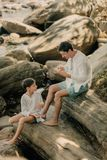 Father and son are playing on rocks. Near the ocean Stock Photos