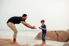 Father and son playing on the rocky beach. Shot of father and son playing on the rocky beach. Young men with little boy having fun at the sea shore Stock Photography