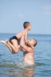 Father and son playing at the sea Stock Photography