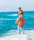 Father and son playing in the sea. Father and his son playing in wave in the sea. Concept of friendly family Stock Image
