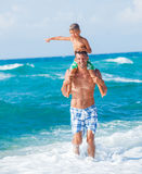 Father and son playing in the sea. Father and his son playing in wave in the sea. Concept of friendly family Royalty Free Stock Image