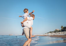 Father with son playing on the sea surf line together Royalty Free Stock Photos