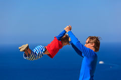 Father and son playing on sea vacation stock photo