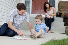 Father and Son Playing on Sidewalk. Young Father And Son Drawing With Chalk And Mother Sitting With Baby At Background In Front Of Their House Royalty Free Stock Photos