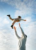 Father and son playing on sky background Stock Photos