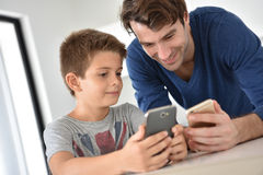 Father and son playing on smartphone Royalty Free Stock Photography