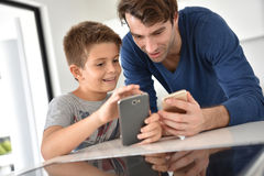 Father and son playing on smartphone Royalty Free Stock Image