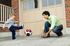 Father and son playing soccer. Father teaching son to play soccer on driveway Stock Photography