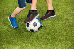 Father and son playing soccer on grass Stock Photography