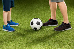 Father and son playing soccer on grass Royalty Free Stock Images
