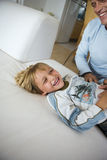 Father and son (6-8) playing on sofa at home, smiling, side view (tilt) royalty free stock image