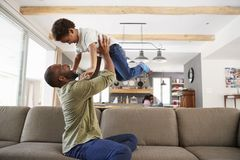 Father And Son Playing On Sofa In Lounge Together Royalty Free Stock Photo