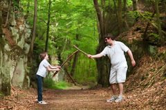 Father and son playing with sticks on hike in park Royalty Free Stock Photography