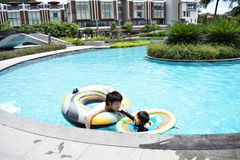 Father and son playing at summer pool. Japanese father and son playing at summer pool Royalty Free Stock Photos