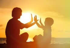 Father and son playing at sunset sea Stock Image