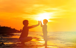 Father and son playing at sunset sea Stock Photography