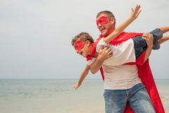 Father and son playing superhero on the beach at the day time. Royalty Free Stock Images