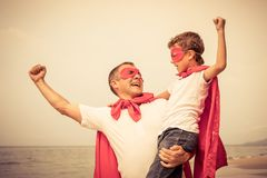 Father and son playing superhero on the beach at the day time. Royalty Free Stock Photos