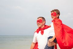 Father and son playing superhero on the beach at the day time. Stock Photo