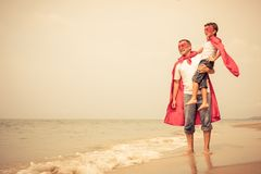 Father and son playing superhero on the beach at the day time. Stock Images