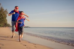 Father and son playing superhero on the beach at the day time royalty free stock photos