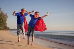 Father and son playing superhero on the beach at the day time stock image